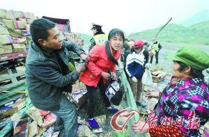 大货车司机试图阻止村民哄抢自己的货物。CFP供图