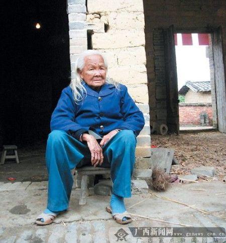 """26日上午,""""死而复生""""的黎秀芬老人默默地坐在家门口。记者 赵敏摄"""