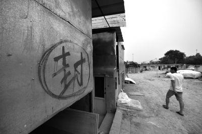 """板房被城管写上了""""封""""字,烂尾楼地下室的大门被封。"""