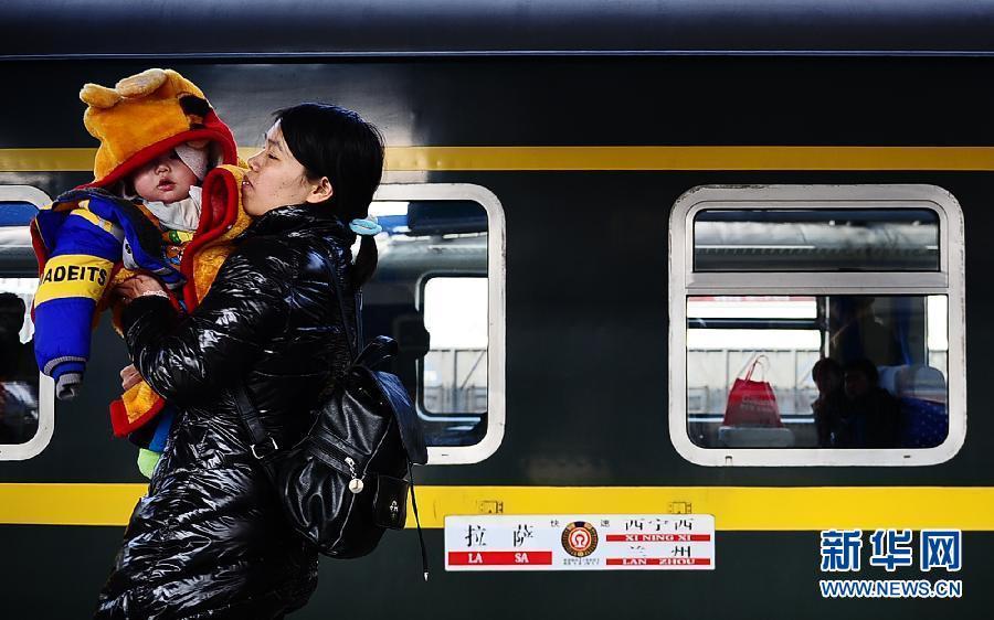 1月27日,一名怀抱小孩的乘客在西宁西客站进站登车