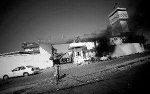 22日,利比亚的黎波里,一辆停靠在女子军事学院旁边的汽车被炸毁。