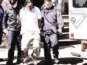 警方下昼1时将一名年约30岁,高约6呎2吋,穿白T恤、灰斜裤的嫌犯从五分局内带出,嫌犯被戴上手铐、脚镣,左手掌有伤。警察将他塞进救护车,送医治伤。(侨报记者叶永康摄)