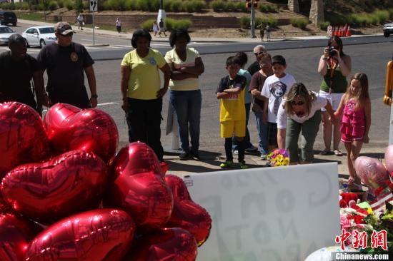 当地时间7月21日,奥罗拉居民在发生枪击案影院外的草坪上点燃蜡烛,摆放上鲜花、毛绒玩具、气球和各种亲情卡片,为遇难者祈祷祝福。中新社发 王欢 摄