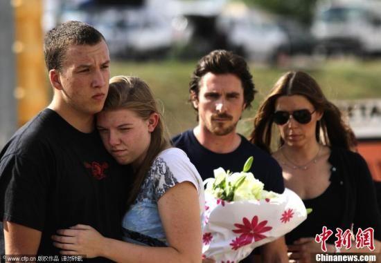 """7月24日,美国奥罗拉,美国演员、""""蝙蝠侠""""的扮演者克里斯蒂安・贝尔Christian Bale造访《蝙蝠侠3》首映礼枪击案遇难者悼念现场,向亡者敬献鲜花。图片来源:CFP视觉中国"""