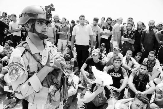 大批伊拉克男子12日聚集在巴格达的征兵中心外,响应政府打击叛军的号召,自愿参军。