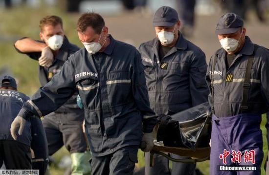 """当地时间2014年7月19日,乌克兰Grabovo,救援人员在马航M17坠机事故的现场。国际社会要求控制马航MH17坠机事故现场的亲俄武装提供独立调查击落该机的凶手提供""""迅速、全面、可靠、畅通无阻的""""配合。"""