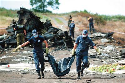 20日,乌克兰紧急部门工作人员在事故现场搬运遇难者遗体,乌民间武装人员在一旁。
