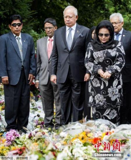 2014年7月31日,荷兰希尔弗瑟姆,马来西亚总理纳吉布携妻子在当地一处军事基地外献花,悼念马航MH17坠机事件遇难者。