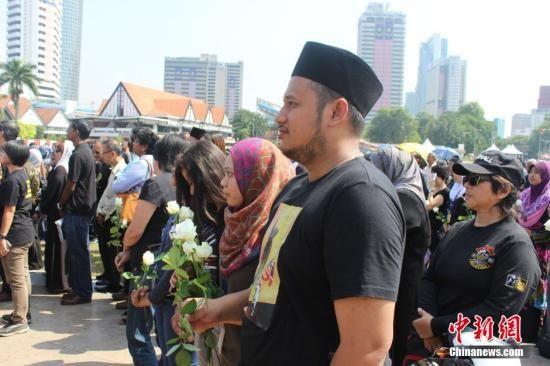 资料图:马来西亚首批MH17罹难者遗体8月22日运回吉隆坡,马来西亚政府将22日定为全国哀悼日。图为民众自发前往吉隆坡独立广场向罹难者致哀。中新社发 赵胜玉 摄