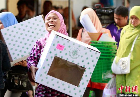 图为7月2日,工作人员在泰国南部也拉府搬运投票箱。