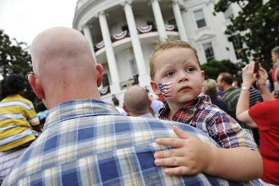 一个参加独立日活动的小孩儿脸上画着美国国旗