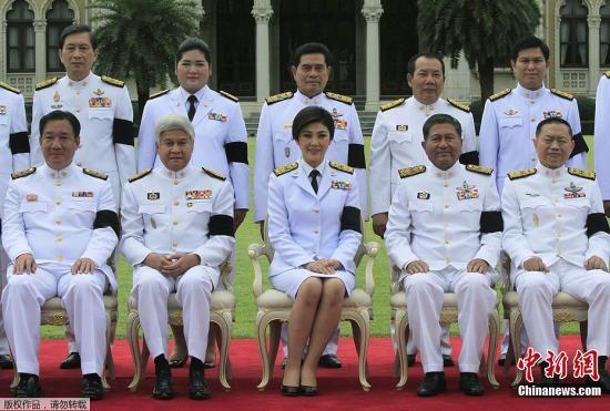 8月10日,泰国曼谷,泰国第一个女总理英拉・西那瓦与新内阁成员一起亮相。 英拉和内阁成员们戴着黑纱,悼念泰国王室成员的死亡。