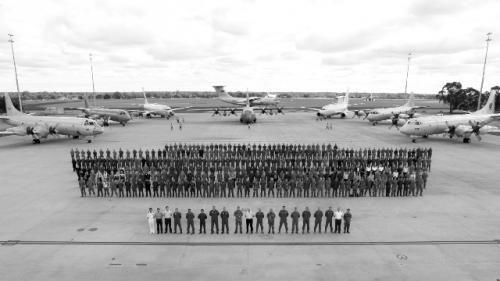 来自至少7个国家的600多名军人在飞机前庄严站立,带着没有找到飞机的失望合影留念