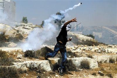 2日,巴勒斯坦约旦河西岸,一名巴勒斯坦人将以色列军队发射的催泪瓦斯弹扔回去。