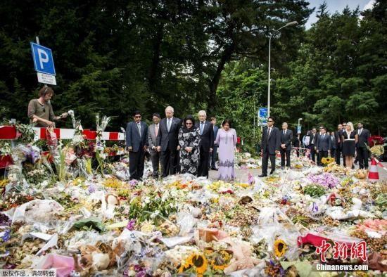 2014年7月31日,荷兰希尔弗瑟姆,马来西亚总理纳吉布携妻子在当地一处军事基地外献花。法医专家正在该基地内对马航MH17失事航班遇难者的遗体进行辨认和恢复。