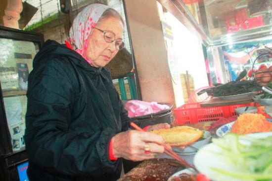 """阮氏禄老太太因出售的三明治物美价廉,被游客们赞为""""三明治女王""""。"""