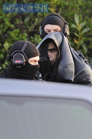 """为防止更多""""独狼""""出现,法国连续逮捕多名极端主义嫌疑人。图为3月30日,警察在法国库埃龙市展开突击行动,逮捕一名嫌疑人。法新社"""
