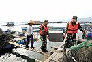官兵在帮助渔民转移渔具