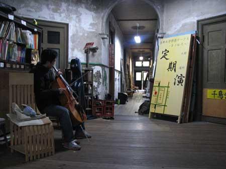 小楼的一层,一个学生正在拉大提琴.