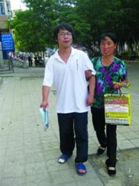 昨日下午,考完数学科目的王闯光脚穿着拖鞋一瘸一拐地走出考场,母亲赶紧上前扶住儿子。 记者 徐月姣 摄