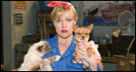 A lady holding a dog and a cat