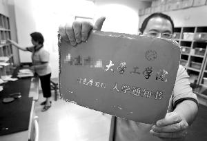 """邮局工作人员展示一份印有""""特色学习班""""字样的山寨版录取通知书"""