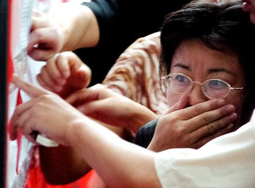 2005年6月25日,南京,小升初电脑派位现场,母亲紧张地寻找孩子的名字。 摄影/石睿 供图/IC
