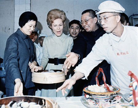 Pat Nixon, wife of former US President Richard Nixon, lifts a bamboo steamer of food at the Hotel Peking kitchen while listening to a cook and interpreter explain how the food is prepared, Feb 22, 1972. 1972年2月22日,美国前总统理查德・尼克松的妻子帕特在北京饭店的厨房内端起了一个蒸笼,并听厨师和口译介绍食物是如何做出来的。