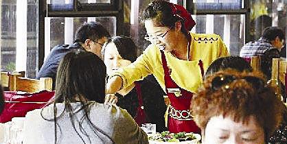 女硕士在火锅店服务。《东方今报》供图