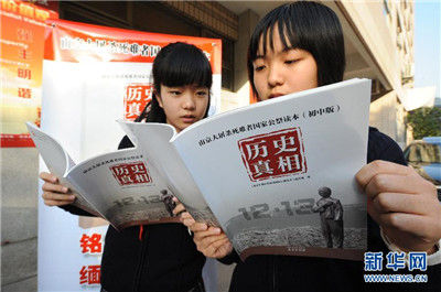11月13日,南京外国语学校两名学生在阅读她们刚刚领取的《南京大屠杀死难者国家公祭读本》(初中版)。