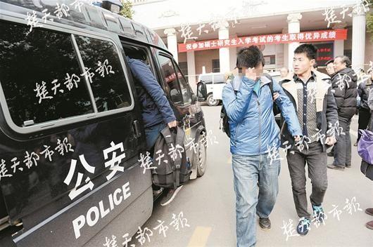 图为:违规考生被便衣民警带上警车