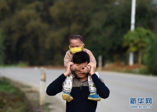 在广西大化瑶族自治县大化镇景山村,韦康仁背着生病的弟弟散步(2月22日摄)。