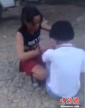 初中生被黑衣红裙的女子��打耳光。 视频截图 摄