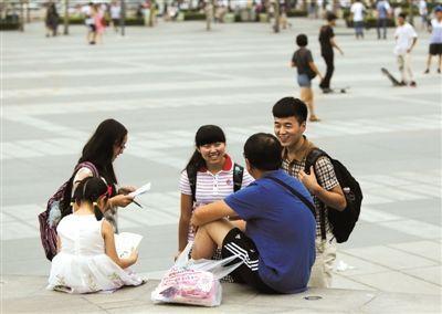 """8月1日,""""生存""""活动最后一天,张阳(右一)和同伴在西单广场与市民交流。"""