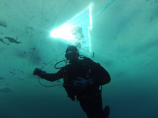 探险者由冰冻的湖面上凿开的洞口潜入冰冷的湖水中工作(网页截图)