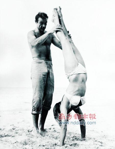 """来吧,邦女郎 肖恩・康纳利在《诺博士》的拍摄现场与邦女郎扮演者乌苏拉・安德丝在沙滩玩耍。倒立?简单,邦女郎来吧,""""我教你""""。"""