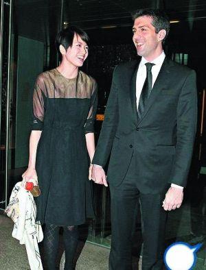 情人节晚餐吃了两个小时,梁咏琪离开时拿着老公送的玫瑰花。