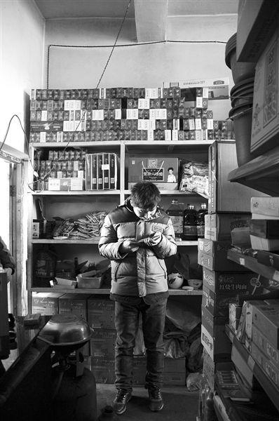 1月21日,周玮在自家的超市里玩计算器。