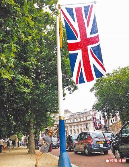 蔡依林在伦敦海军拱门林荫大道前,作势推旗杆。