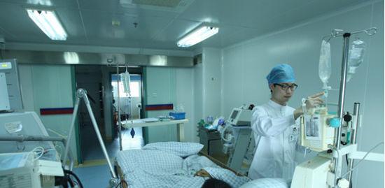 男护士刘坚在icu病房内照料病人