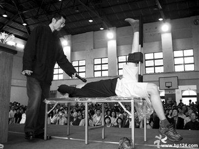 """萧宏慈在向学员讲解示范""""拉筋凳""""的使用。他称,拍打拉筋治百病。本版图片来源""""医行天下/萧宏慈""""博客等"""