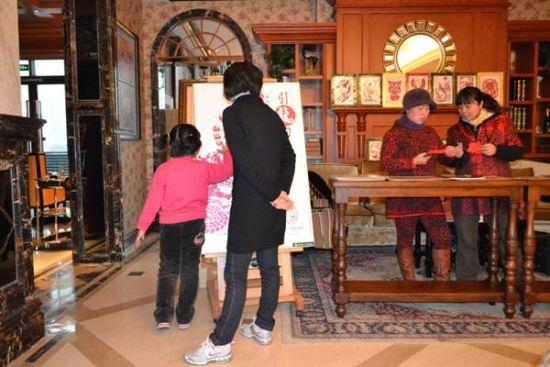 一对家长和小朋友在讨论剪纸图案