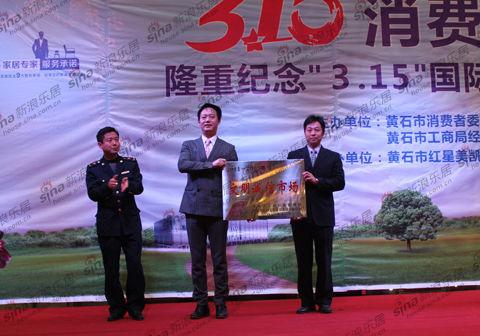 红星美凯龙黄石商场联合党支部书记姜辉与商场总经理徐曜晖共同上台接受授牌
