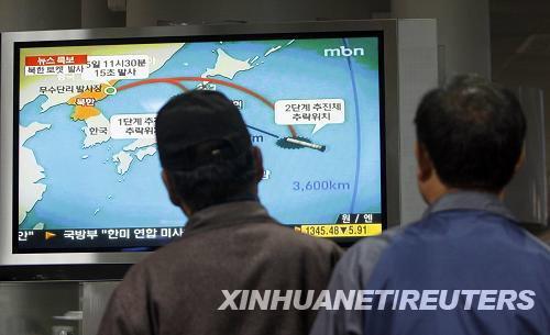 4月5日,两名韩国人在首都首尔的火车站观看朝鲜发射人造卫星的电视新闻。
