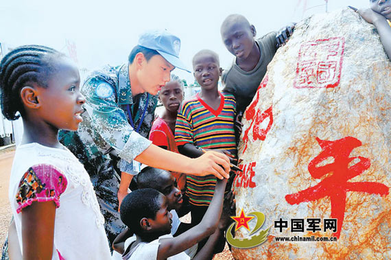 China's ninth batch of peacekeepers to Liberia and the officers and men engineering unit local people of the book of peace, to express wishes. Liu Song photo