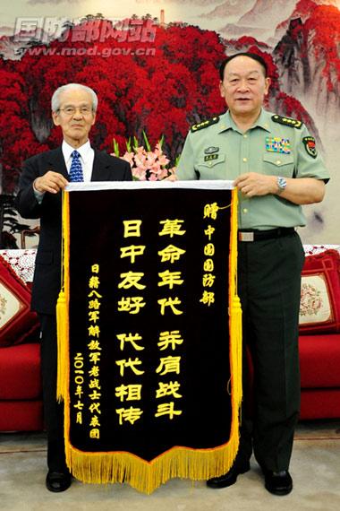 7月29日,国务委员兼国防部长梁光烈上将在八一大楼接受来访的日本籍老战士代表团赠送的锦旗。李晓伟摄