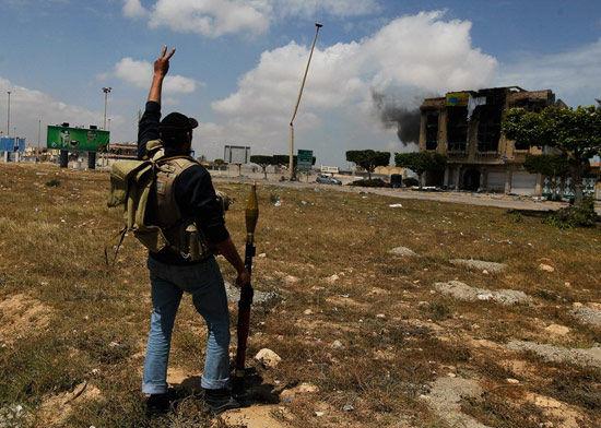 资料图:一名利比亚反对派武装人员作战期间打出胜利手势。