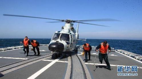 """4月25日,在中俄海上联合实兵演习中,直升机准备在""""哈尔滨""""舰飞行甲板上起飞。当日,参加中俄海上联演实兵演练的中、俄舰艇编队进行联合防空、联合补给、联合反潜等多项课目的演练。 新华社记者 吴登峰 摄"""