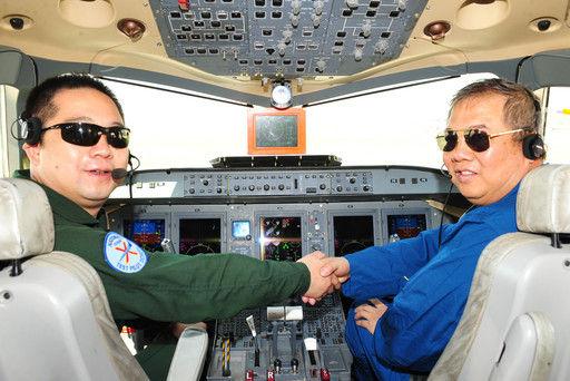吴光辉(右)在飞行体验开始前与ARJ21首席试飞员赵鹏握手预祝飞行成功。刘其东 摄