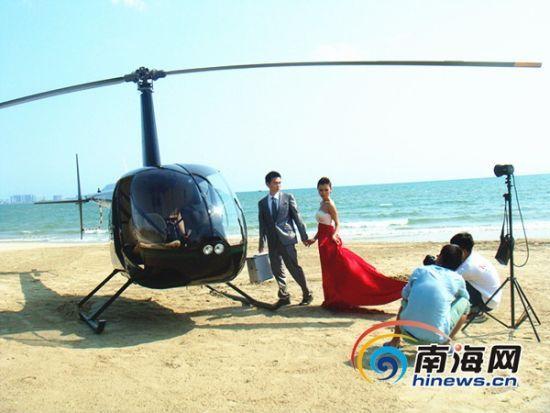 直升机停靠下三亚湾沙滩,引来不少情侣前来拍婚纱照。